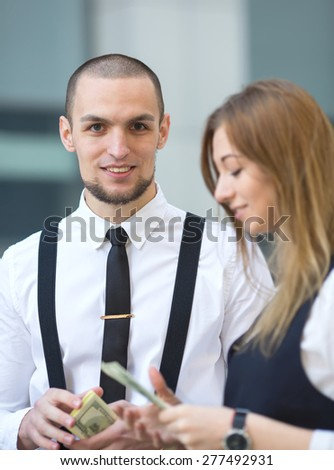 Man receiving money, US dollars. Business man holding a money hundred dollar banknotes. Businessman and businesswoman on blurring background office building work. They count the money and divide. - stock photo
