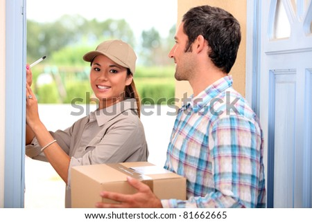 man receiving package from a delivery girl - stock photo