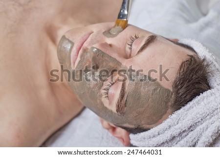 man receiving spa facial treatment - stock photo