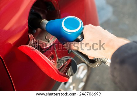 Man Refilling The Red Car With Fuel At Gas Station - stock photo
