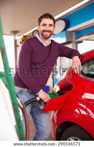 Man refuelling a car at a petrol station - stock photo