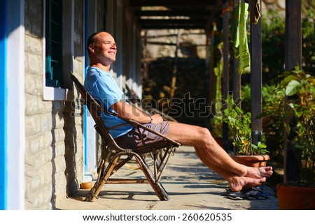 man relaxed and enjoy in chair at the sunny morning in patio - stock photo