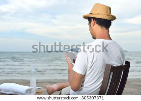 Man relaxing and use tablet computer at beautiful tropical beach - stock photo