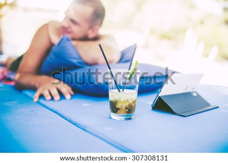 Man relaxing and use tablet computer at beautiful tropical beach and drinking mojito - stock photo