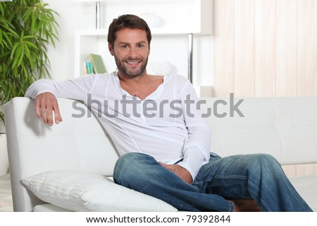 Man relaxing at home sitting on sofa - stock photo
