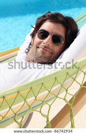 Man relaxing by the pool - stock photo