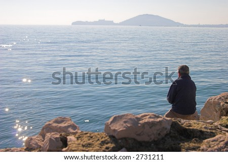 Man relaxing by the sea. Sunny day. - stock photo