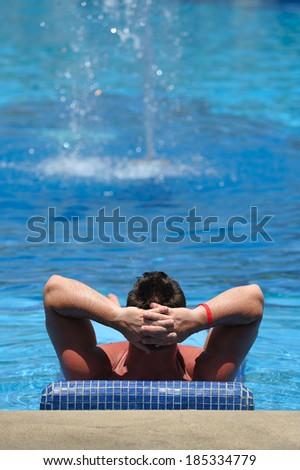 Man relaxing in a swimming pool (your text on top of the image) - stock photo
