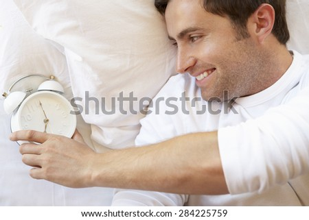 Man Relaxing In Bed With Alarm Clock - stock photo
