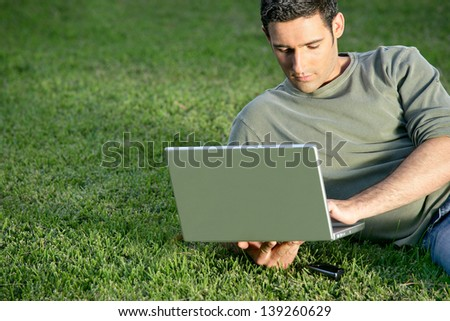 Man relaxing in field with laptop - stock photo