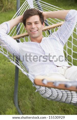 Man relaxing in hammock smiling - stock photo