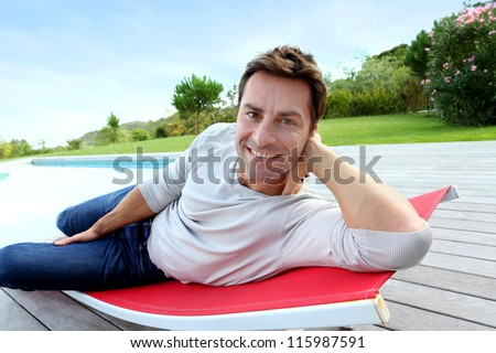 Man relaxing in long chair by pool