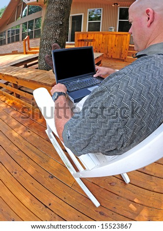 Man relaxing in rocker working on laptop computer on outside deck - stock photo