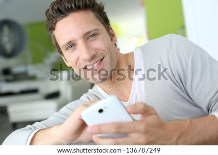 Man relaxing in sofa and reading his emails - stock photo