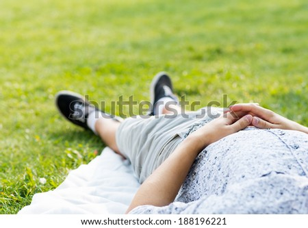 man relaxing in the park, close-up of linked hands on his stomach - stock photo