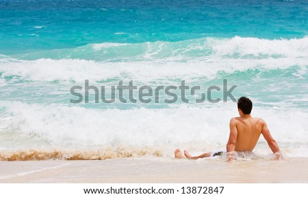 Man relaxing in the water on the beach looking at sea waves