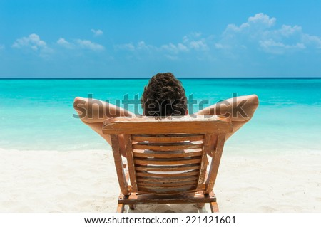 Man relaxing on beach, ocean view, Maldives island - stock photo
