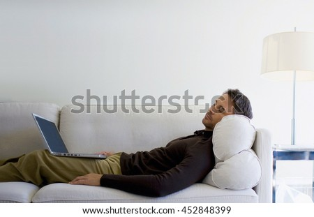 man relaxing on his bed with laptop at home in bedroom - stock photo