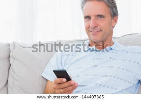 Man relaxing on his couch sending a text smiling at camera using smartphone - stock photo