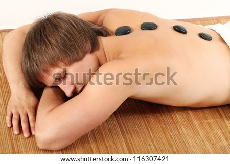 Man relaxing on massage bed with hot stones isolated over white background - stock photo