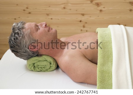 Man relaxing on massage bench, portrait - stock photo