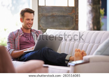 Man Relaxing On Sofa At Home Using Laptop Computer - stock photo