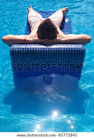 Man relaxing on swimming pool sunbed - stock photo