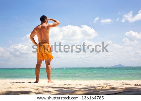 Man relaxing on the beach looking at sea. - stock photo