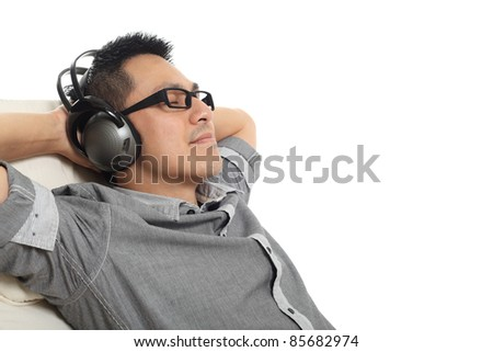 Man relaxing on the sofa and listening to music. Isolated on white background. - stock photo