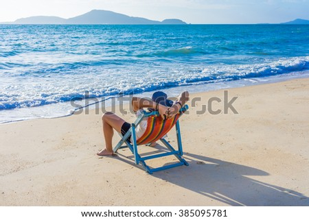 Man relaxing on the tropical beach, ocean view - stock photo