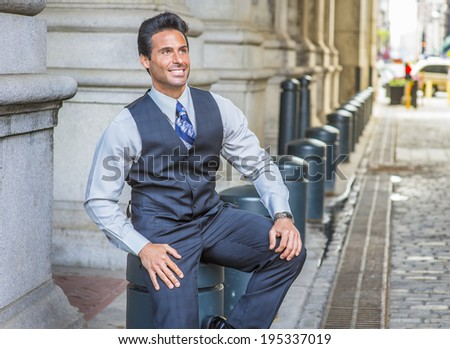 Man Relaxing Outside. Dressing in light gray shirt, dark blue vest, necktie, a handsome, middle age businessman is sitting on metal column on street,  smiling, looking up.  - stock photo