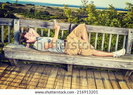 Man Relaxing Outside. Wearing a gray T shirt, yellow pants, white sneakers, a young guy is lying down on wooden bench against fence in remote location, checking messages on mobile phone. - stock photo