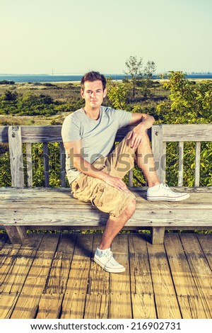 Man Relaxing Outside. Wearing a gray T shirt, yellow pants, white sneakers, a young handsome guy is sitting on wooden bench against fence in remote location, a foot on bench, looking at you.  - stock photo