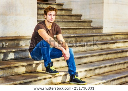 Man Relaxing Outside. Wearing dark brown T shirt, blue jeans, black sneakers, a young sexy guy with curly hair is sitting on stairs outside office, waiting for you.  - stock photo
