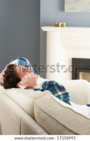 Man Relaxing Sitting On Sofa At Home Talking On Phone - stock photo