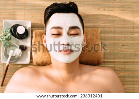 Man relaxing with facial mask on, view from the top - stock photo
