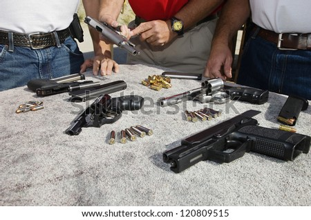 Man reloading handgun with troops standing together - stock photo