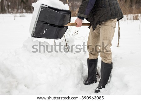 man removes shoveling snow from the track, using a spade in the winter in the village - stock photo