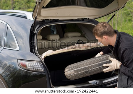 Man removing his spare tyre from the open boot of his hatchback car after suffering a puncture on a country road - stock photo