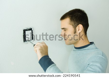 Man removing light switch cover - stock photo