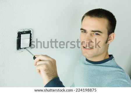 Man removing light switch cover from wall - stock photo