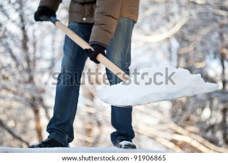 Man removing snow from a driveway with a shovel - stock photo