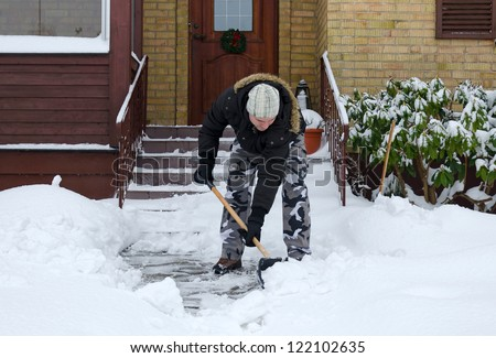 Man removing snow in front of his house - stock photo