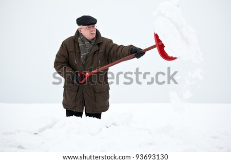 Man removing snow with a shovel after hard snowfall - stock photo