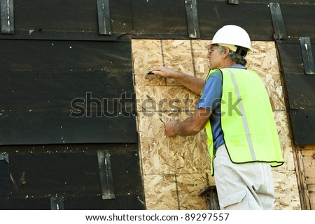 man removing tar paper from an old building