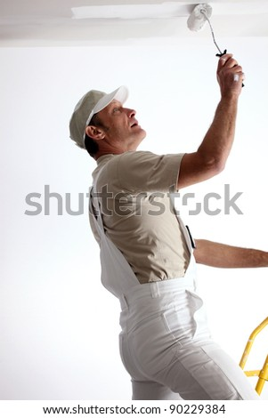 Man repainting ceiling with roller - stock photo