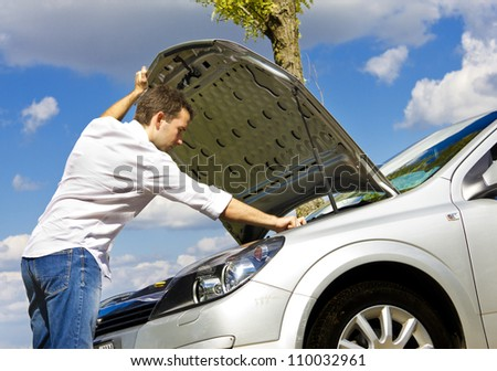 Man repairing a broken car by the road - stock photo