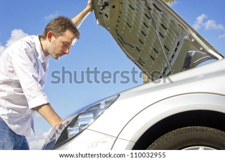 man repairing a broken car on a road - stock photo