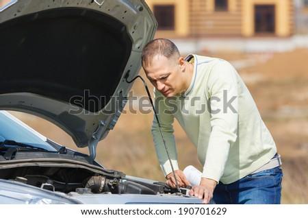 man repairing a broken car on the road - stock photo