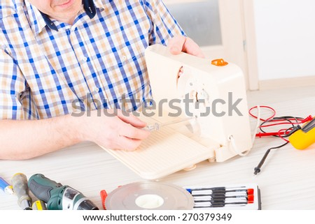 Man repairing a slicing machine at home appliance service workshop - stock photo
